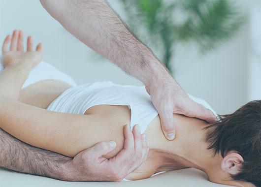 Chiropractor Stretching A Womans Shoulder